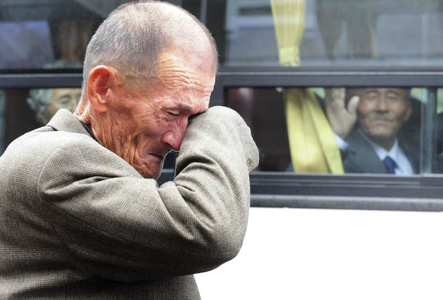 A North Korean man waves his hand as a South Korean relative weeps, following a luncheon meeting during inter-Korean temporary family reunions at Mount Kumgang resort October 31, 2010. Four hundred and thirty-six South Koreans were allowed to spend three days in North Korea to meet their 97 North Korean relatives, whom they had been separated from since the 1950-53 war.
