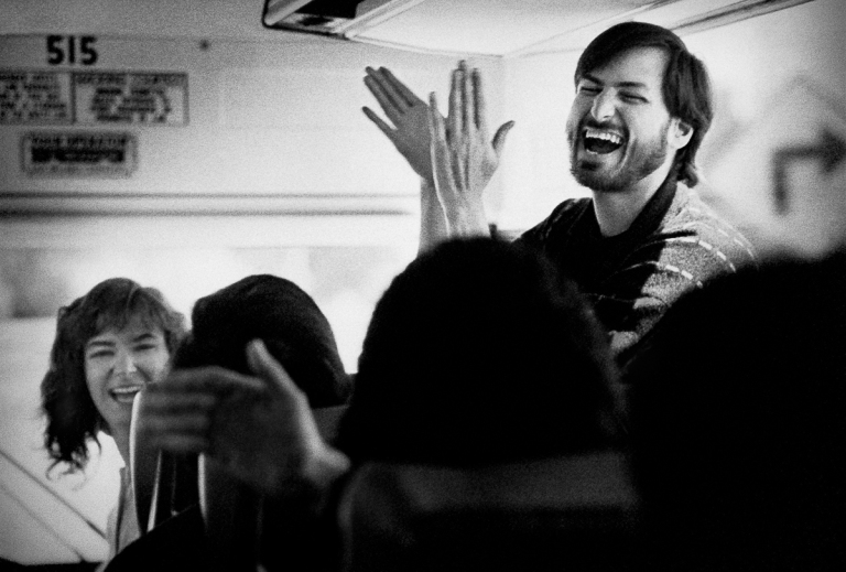 PALO ALTO:  NeXt CEO Steve Jobs and Susan Barnes, NeXt VP and CFO, reacting to a joke tod by an employee on the bus going back to the headquarters in Palo Alto, CA. The team was visiting the unfinished factory in Fremont in March 1987.(Photo by Doug Menuez, Contour by Getty Images)
