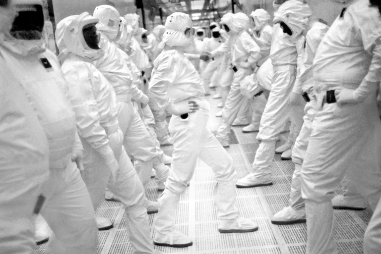 1998 Workers inside Intel's largest chip fabrication plant exercise and stretch as part of their normal workday break time. They produce five chips per second, 24 hours per day. Many of the workers are from the nearby Pueblo tribe of Native Americans, who maintain their traditions when not working with new technology. After work, in good weather, many tend their corn and bean fields with their families before dinner. IMAGE: DOUG MENUEZ/CONTOUR BY GETTY IMAGES