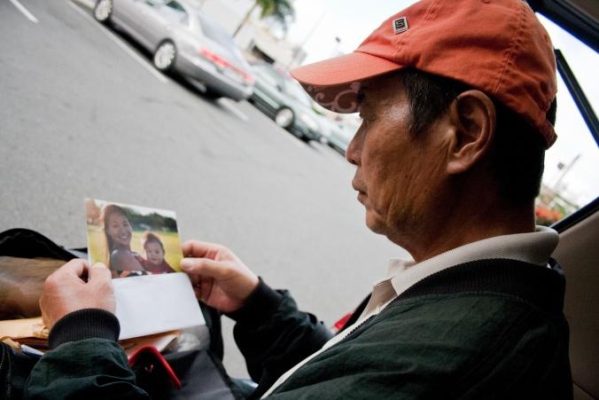 """Kim's father looks at family photos. Photo courtesy of Diana Kim, """"The Homeless Paradise."""""""