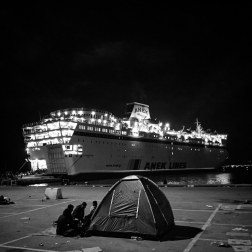 Refugees camp out near the Eleftherios Venizelos, in Mytilini, Greece. The ship is transporting 2500 refugees to Athens. The schedule is irregular, adding to the confusion. Patrick Witty