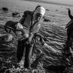 A woman carries her child to safety after landing on the coast of Lesbos, Greece. Patrick Witty