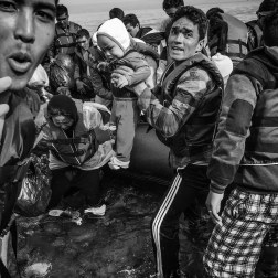Refugees scramble off the boat, passing the children to the shore. Patrick Witty for BuzzFeed News