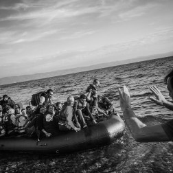 An aid worker rushes to assist a boat filled with refugees as it lands on the coast of Lesbos, Greece. Depending on where the boats land, aid workers and journalists scramble to meet the boat along the rocky coast of Lesbos, Greece. Patrick Witty for BuzzFeed News