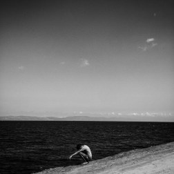 A refugee rests along the coast as he makes the walk towards a camp to wait for a bus to Mytilini, a larger town at the other end of the island of Lesbos. Patrick Witty for BuzzFeed News