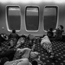 Refugees sleep throughout the ship during the 10 hour journey to Athens. Patrick Witty