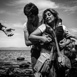 A woman is helped to the shore after a boat filled with refugees landed on the shore of Lesbos, Greece. Patrick Witty for BuzzFeed News