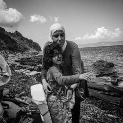 A mother removes a life jacket made from Styrofoam blocks and tape from her daughter after landing in Lesbos, Greece. Patrick Witty for BuzzFeed News