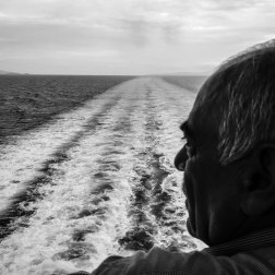 A man looks out on the horizon at the rear of the El. Venizelos on the journey to Athens. Many refugees choose to sleep on the deck due to the temperature inside the ship. Patrick Witty