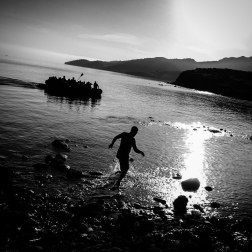 An aid worker rushes to assist a boat filled with refugees as it lands on the coast of Lesbos, Greece. Thousands of people arriving by boat have passed through the island this year. Patrick Witty For Buzzfeed