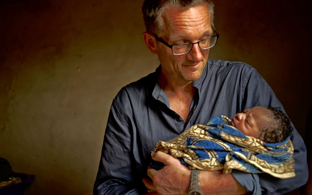 Programme Name: Countdown To Life: The Extraordinary Making Of You - TX: n/a - Episode: 9 Months That Made You - generics (No. n/a) - Picture Shows: ...meets the newest arrival to the Gambia Michael Mosley - (C) BBC - Photographer: David Barker