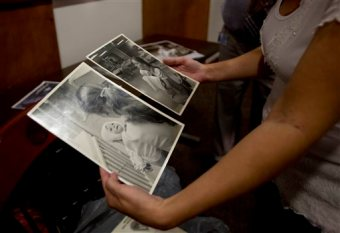 Amanda Scarpinati holds old photographs of herself being held by a nurse before a news conference at Albany Medical Center on Tuesday, Sept. 29, 2015, in Albany, N.Y. The upstate New York woman who suffered severe burns as an infant is finally getting the chance to thank the hospital nurse who cared for her, thanks to a social media posting that revealed the identity of the nurse in 38-year-old photos. (AP Photo/Mike Groll)