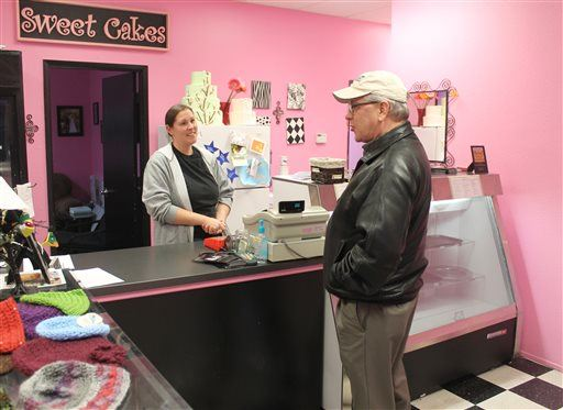 This photo taken Feb. 5, 2013, shows Melissa Klein, co-owner of Sweet Cakes by Melissa in Gresham,Ore., telling a customer  that the bakery has sold out of baked goods to sell for the day. An administrative law judge proposed Friday, April 24, 2015, that the owners of the suburban Portland bakery pay $135,000 to a lesbian couple who were refused service more than two years ago. The judge, Alan McCullough, ruled in January that Sweet Cakes by Melissa discriminated against Laurel and Rachel Bowman-Cryer by refusing to bake them a wedding cake. The bakers cited their religious beliefs in a case that has been cited in the national debate over religious freedom and discrimination against gays. (Everton Bailey Jr./The Oregonian via AP)