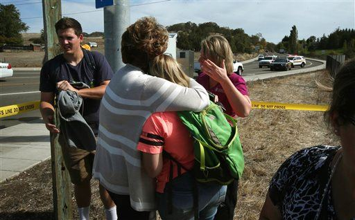 Bystanders console each other on a road leading to the Umpqua Community College campus in Roseburg, Ore. Thursday, Oct. 1, 2015, following a deadly shooting at the school. (Chris Pietsch /The Register-Guard via AP) MANDATORY CREDIT