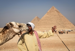 An Egyptian guide nuzzels with his camel on the outskirts of Cairo.