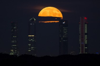 The supermoon - so called because it is the closest full moon to the Earth this year - rises between towering buildings in Madrid, Spain.