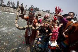Peruvian shamans holding a figure of a Nino Jesus and a snake during a ritual to fight the negative effects of El Nino weather.