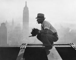 """Charles Ebbets preparing for his """"Lunch atop a Skyscraper"""" photograph in 1932. He is perched on the 69th floor of the GE building."""
