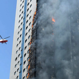 A helicopter hovers over a skyscraper which caught fire in Sharjah, United Arab Emirates.