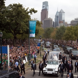 Pope Francis waves to revelers as he he drives along Benjamin Franklin Parkway to lead Mass in Philadelphia.