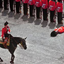 A British foot guard passes out as Queen Elizabeth II rides past during the colour parade in June, 1970.