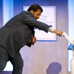 "Astrophysicist Neil deGrasse Tyson fist-bumps ""Pepper"", a social humanoid robot, during the Clinton Global Initiative's annual meeting in New York."