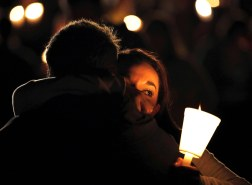 A Umpqua Community College student is comforted during a candlelight vigil for those killed during a shooting in Roseburg, Oregon.