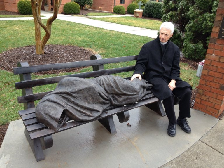 The Rev. David Buck sits next to the Jesus the Homeless statue that was installed in front of his church, St. Alban's Episcopal, in Davidson, N.C. John Burnett/NPR