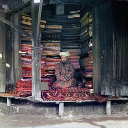 1911 A merchant at the Samarkand market displays silk, cotton and wool fabrics as well as a few traditional carpets. A framed page of the Koran hangs at the top of the stall. IMAGE: PROKUDIN-GORSKII / LIBRARY OF CONGRESS>
