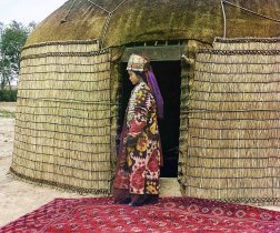 1907-1915 Prokudin-Gorksii captures the traditional dress, jewelry and hairstyle of an Uzbek woman standing on a richly decorated carpet at the entrance to a yurt, a portable tent used for housing by the nomadic peoples of Central Asia. After conquering Turkestan in the mid-1800s, the Russian government exerted strong pressure on the nomadic peoples to settle permanently in villages, towns and cities. IMAGE: PROKUDIN-GORSKII / LIBRARY OF CONGRESS>
