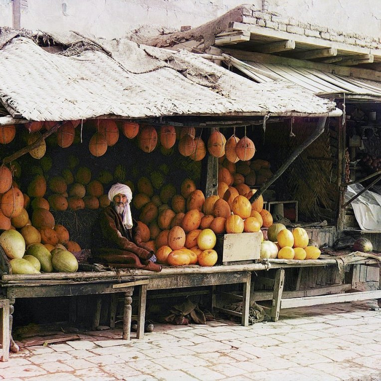 1911 Dressed in traditional Central Asian attire, a vendor of locally grown melons poses at his stand in the marketplace of Samarkand in present-day Uzbekistan. IMAGE: PROKUDIN-GORSKII / LIBRARY OF CONGRESS>