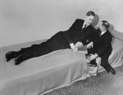 Nineteen year old Robert Wadlow (height 8 ft 7 in) the tallest person in recorded history, chatting with a friend after appearing at a charity event in Omaha, Nebraska, April 1, 1937. He grew another 4 inches before his death three years later.