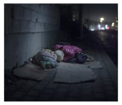 """Beirut. Ralia, 7, and Rahaf, 13, live on the streets of Beirut. They are from Damascus, where a grenade killed their mother and brother. Along with their father, they have been sleeping rough for a year. They huddle close together on their cardboard boxes. Rahaf says she is scared of """"bad boys,"""" at which Ralia starts crying."""