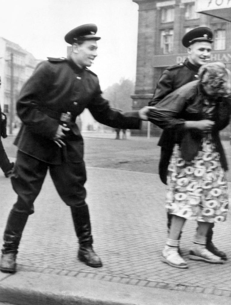 Deuschland, Besatzung 1945-1948, Sowjet. Besatzungszone: Sowjetische  Soldaten belaestigen vor der Westhalle am Hauptbahnhof in Leipzig eine Passantin. Aufnahme 1945/46