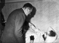 Hitler comforts a frostbitten German soldier who tries to salute him while in bed. Hitler gently sets his arm down to tell him to rest and recover. [c. 1940's]